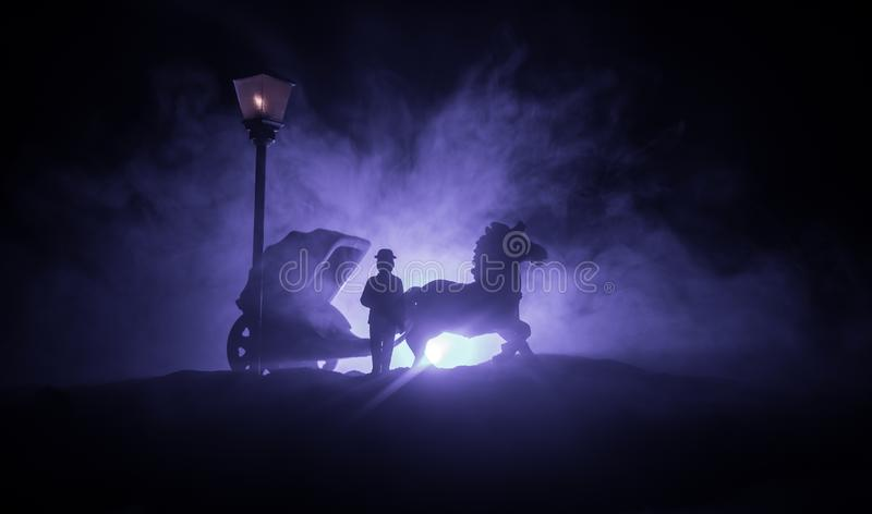 Artwork decoration. Silhouette of old coach with horse on dark toned foggy background. Selective focus royalty free stock images