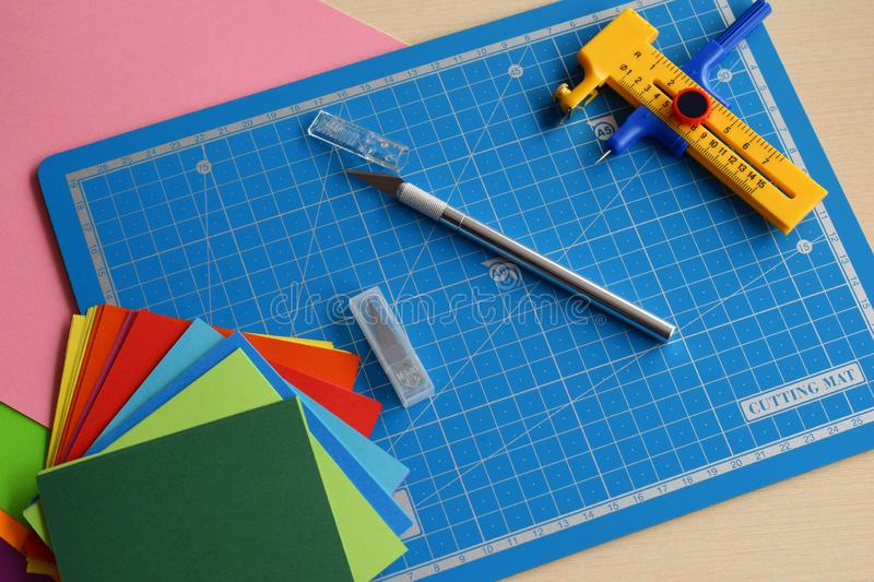 Artwork equipment and tools for paper cut - cutting knife, sharp box cutter, blue cutting plate, origami paper. Modern 3d origami royalty free stock photo