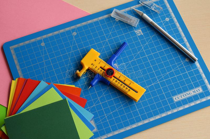 Artwork equipment and tools for paper cut - cutting knife, sharp box cutter, blue cutting plate, origami paper. Modern 3d origami stock photo