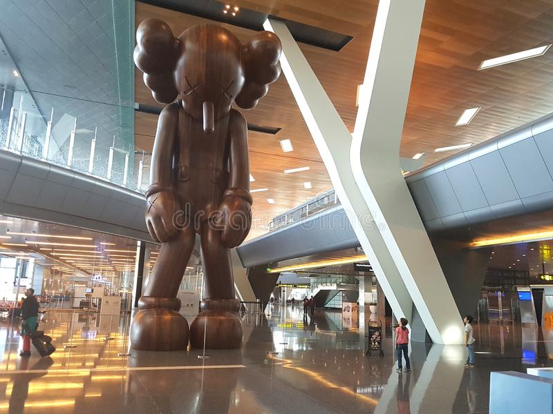 Artwork on show at Doha airport, picture of the monumental wooden art piece called SMALL LIE  by American artist KAWS royalty free stock photography