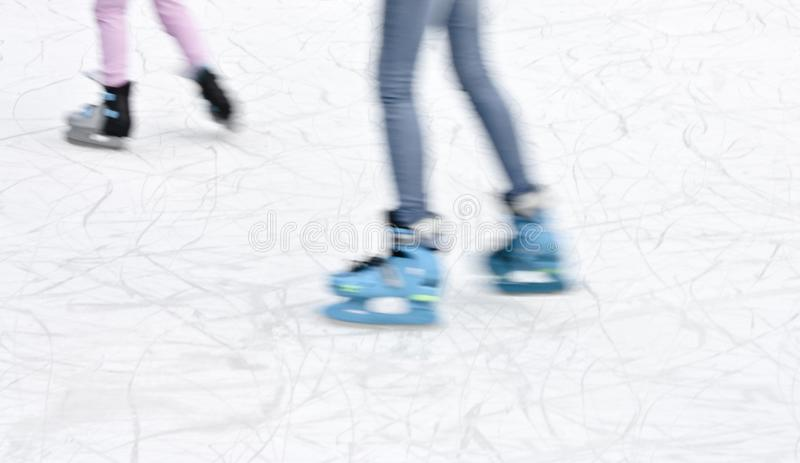 Arty blurry two teenage girl ice skating legs stock photography