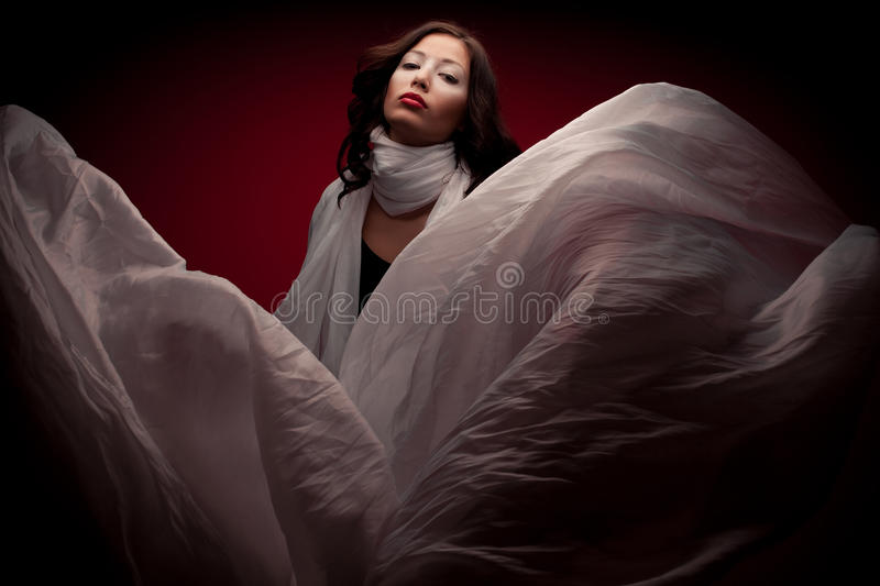 Arty portrait of beautiful brunette with flying white scarf royalty free stock photo