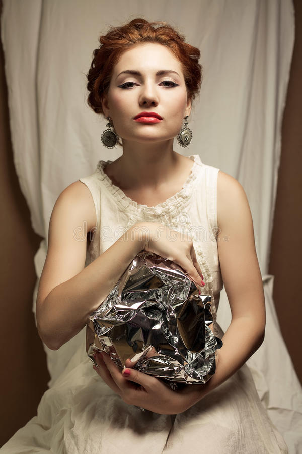 Arty portrait of fashionable queen-like ginger model. Arty portrait of a fashionable queen-like ginger model holding silver foil sphere over white curtain stock images