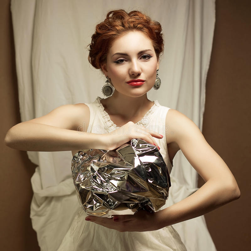 Arty portrait of fashionable queen-like ginger model. Arty portrait of a fashionable queen-like ginger model holding silver foil sphere over white curtain royalty free stock photography
