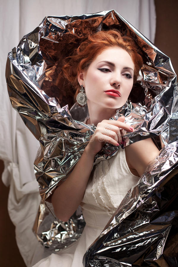 Arty portrait of a fashionable queen-like model with silver foil. Cape over white curtain background. Vintage style. Studio shot royalty free stock photography
