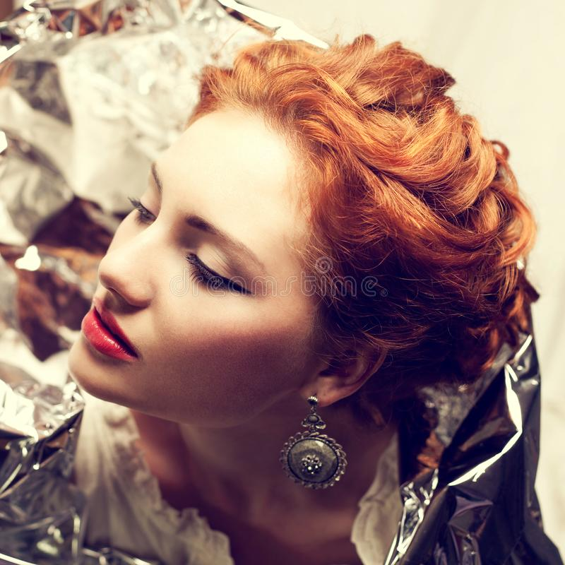 Arty portrait of fashionable queen-like red-haired queen stock photography