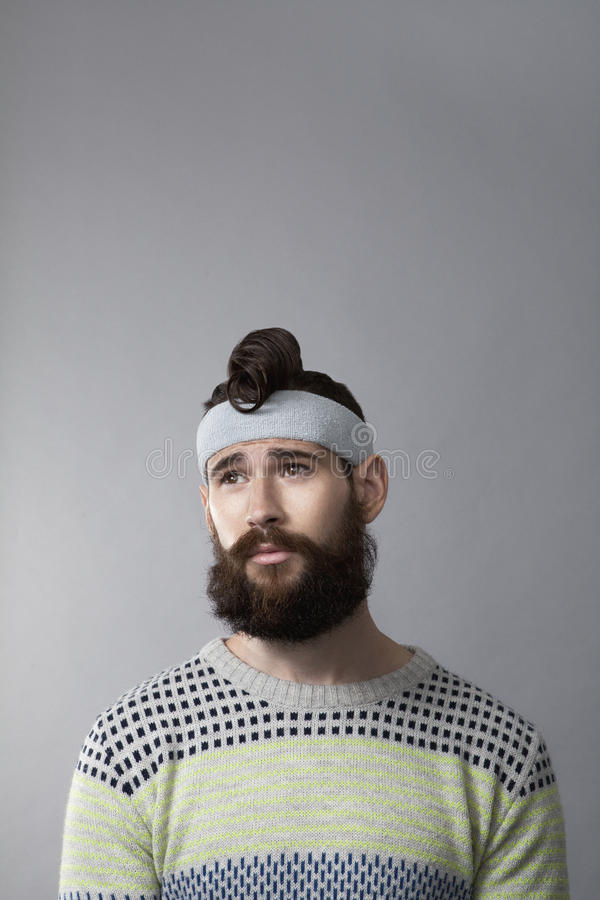 Arty portrait of man with beard. Studio shot of hipster with beard and grey sweatband stock image