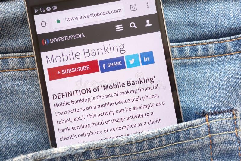 Artykuł o mobilnych bankowość na Investopedia stronie internetowej wystawiającej na smartphone chującym w cajgach wkładać do kies obrazy royalty free
