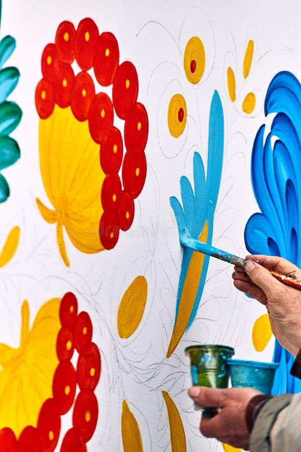 Artysta maluje z nafcianymi farbami na białej ścianie obraz royalty free