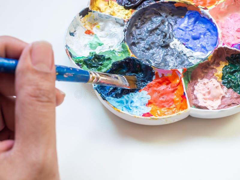 Artysta ręka miesza akrylowej farby kolor z muśnięciem w plastikowej białej sztuki palecie fotografia royalty free