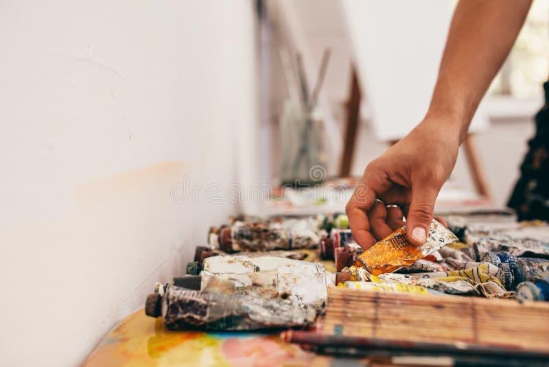 Artysta ręka podnosi up kolor tubki od stołu obraz stock