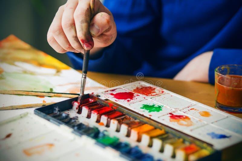 Artysta trzyma pędzel i zbiera czerwoną farbę z palety, a obok jest arkusz ze szkicem i zdjęcia stock