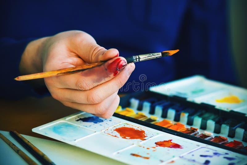Artysta trzyma w ręku pędzel z pomarańczową farbą na końcu A obok jest paleta obrazy royalty free