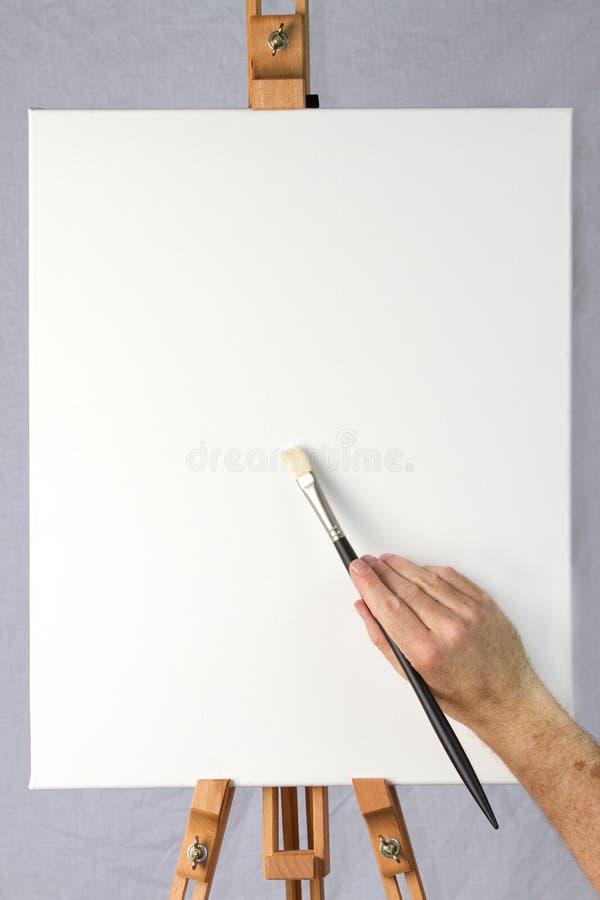 Artysty mienia muśnięcie na pustej kanwie obraz stock