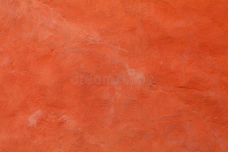 Artystyczny malujący z blaknąć pomarańczowego czerwonego kolor na szorstkiej powierzchni betonowej ścianie dla graficznego projek zdjęcie stock