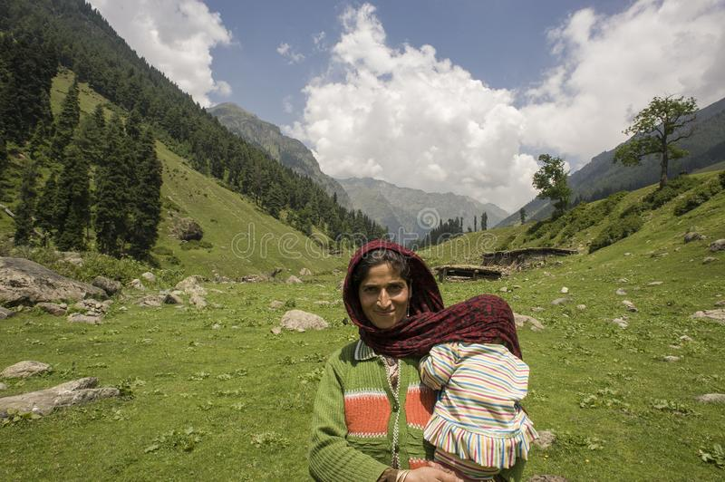 Aru Valley, Pahalgam. Kashmir, India -  August 02, 2011: Gypsy mother of Gujjar ethnicity. Gypsy mother of Gujjar ethnicity with daughter on lap in the Aru royalty free stock images