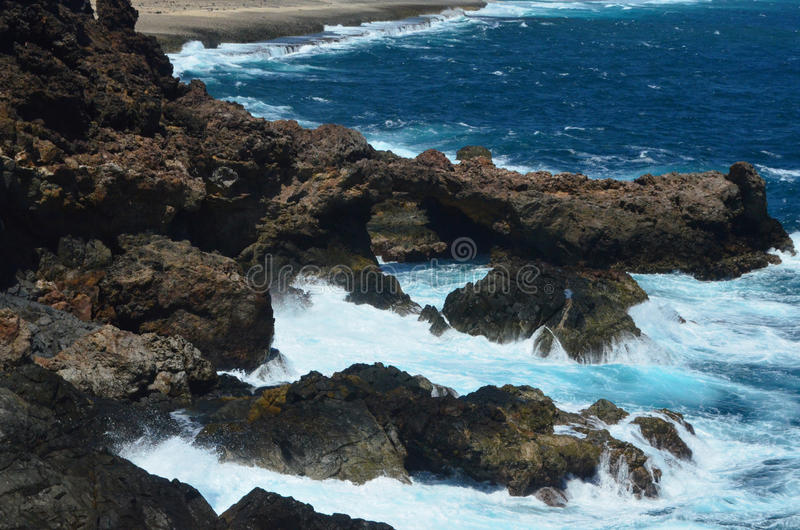 Aruba& x27; s linia brzegowa z law fala i skały Rozbijać obrazy royalty free