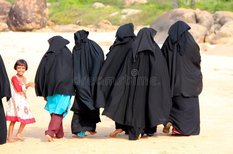 ARUGAM-BAAI, 13 AUGUSTUS: Een groep Moslimvrouwen die onderaan het strand met een klein meisje lopen royalty-vrije stock fotografie