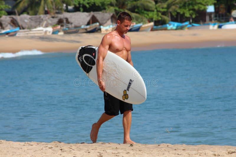 ARUGAM-BUCHT, AM 8. AUGUST: Junger muskulöser Surfer, der sein Surfbrett hält und auf den Strand geht stockbild
