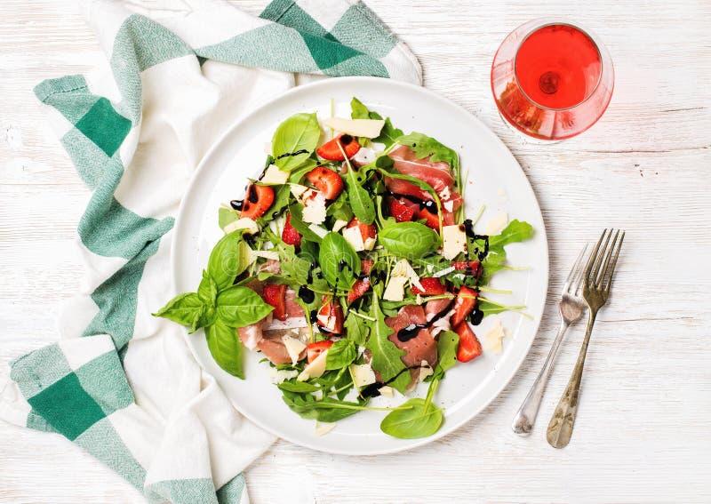 Arugula d'été, prosciutto, salade de fraise avec le verre de vin rosé photo libre de droits