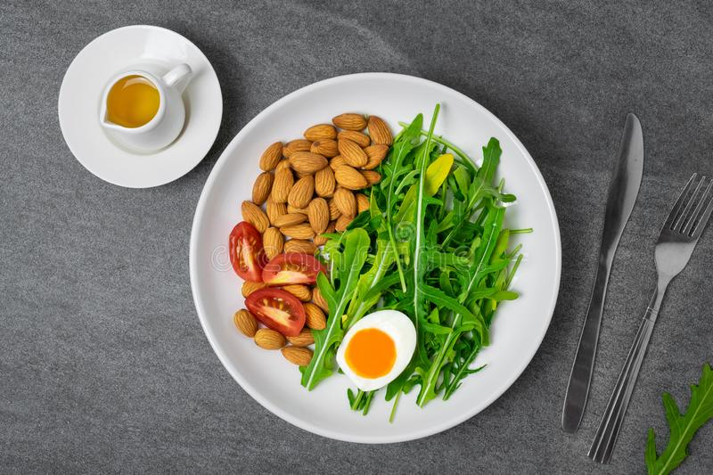 Arugula salad with almonds and tomato,boiled egg in white dish on tile table stock image