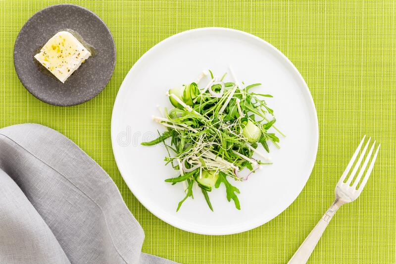 Arugula salad with bean sprout, enoki mushrooms and cucumber, feta cheese on the side, grey napkin and silver fork on green fabric. Arugula salad with bean royalty free stock photos