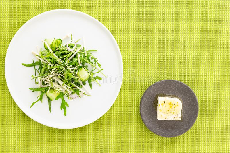 Arugula salad with bean sprout, enoki mushrooms and cucumber, feta cheese on the side over a green fabric. Flat lay with copy. Arugula or rocket salad with bean stock photo