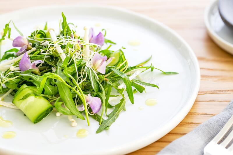 Arugula salad with bean sprout, enoki mushrooms, cucumber and purple edible flowers, over an oak wood background. Arugula salad with bean sprout, enoki royalty free stock photography