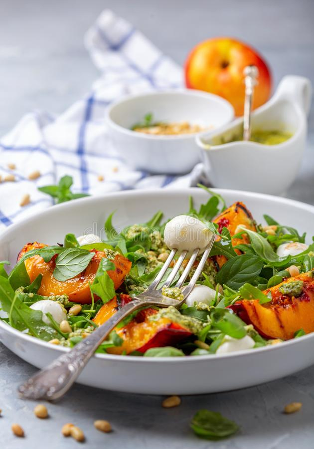 Arugula salad with grilled nectarines. Salad with mint pesto, grilled nectarine, mozzarella and arugula in a plate on a gray textured background, selective focus royalty free stock photography