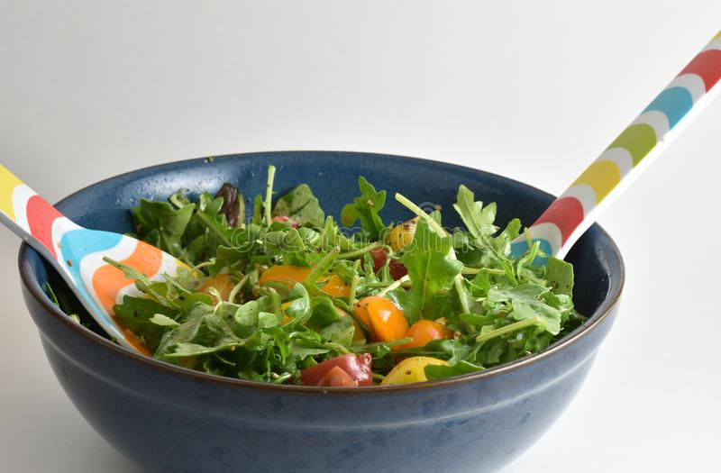 Arugula salad with heirloom tomatoes and lemon dressing in a large mixing bowl. Mixing a healthy salad in a large blue bowl. Arugula salad with heirloom royalty free stock photos