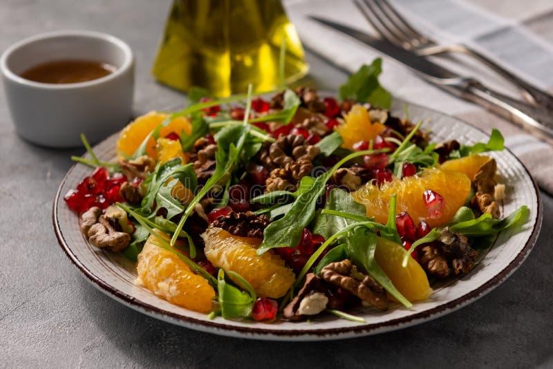 Arugula salad with oranges, walnuts and pomegranate. stock photo