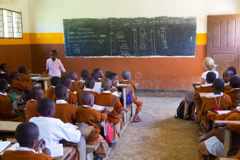 Children in uniforms in primary school classroom listetning to teacher in rural area near Arusha, Tanzania, Africa. Arusha, Tanzania- Jan 26, 2015: Children in stock photo