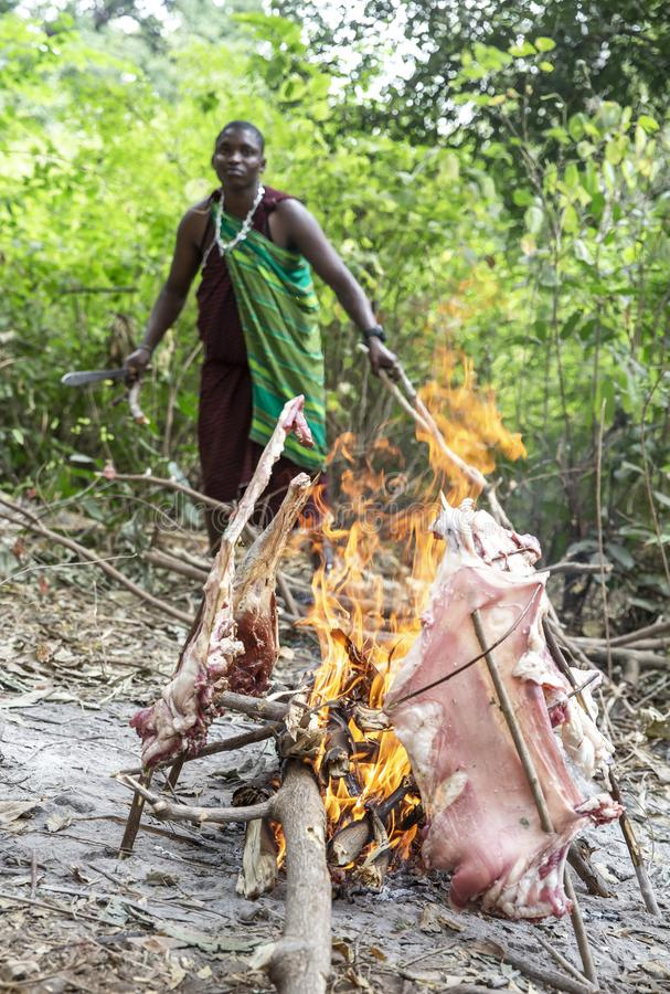 Old maasai man cooking meat on fire stock images