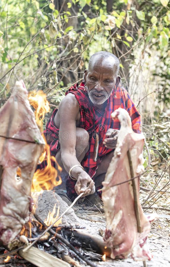 Old maasai man cooking meat on fire stock image