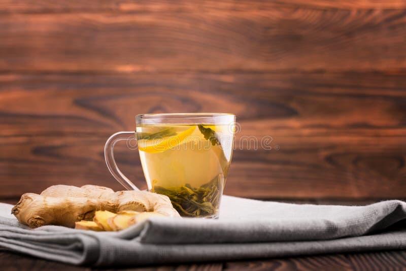 arvense杯子木贼属植物重点玻璃草本马尾注入naturopathy有选择性的茶 甜柠檬茶和裁减姜在木背景 一个杯子姜茶 自然和热的饮料早餐 免版税图库摄影