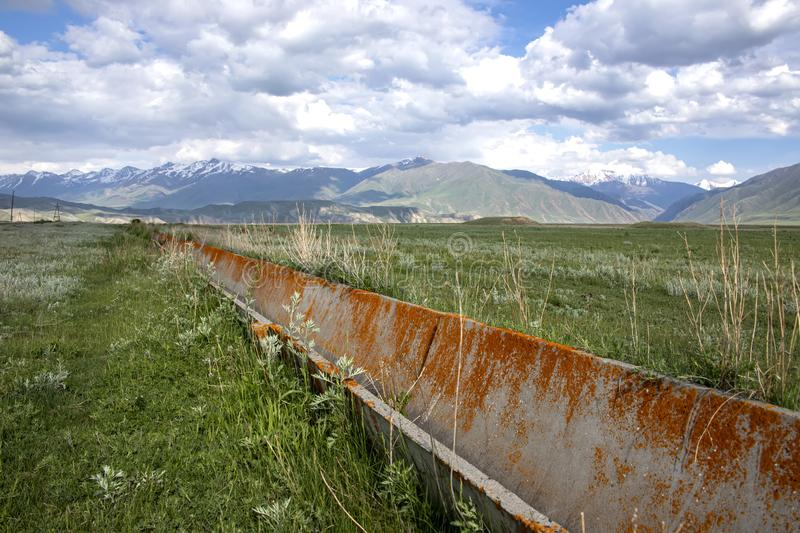 Aryk pecked by lichen on a green valley on a background of hills and mountains with snowy peaks. And a cloudy sky. Traveling in Kyrgyzstan stock image