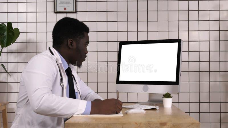 Arzt, der die Kenntnisse oben schauen Informationen über seinen Computer nimmt Weiße Bildschirmanzeige lizenzfreies stockfoto