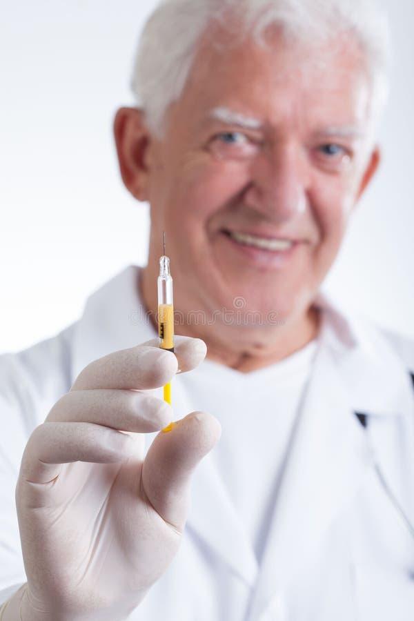 Arzt, der eine Spritze hält lizenzfreie stockbilder