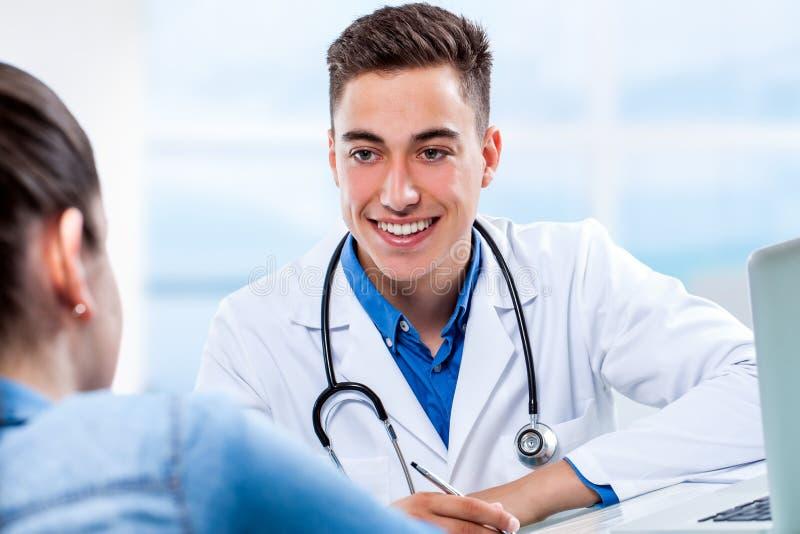 Arzt, der an weiblichem Besuch am Schreibtisch teilnimmt lizenzfreies stockfoto