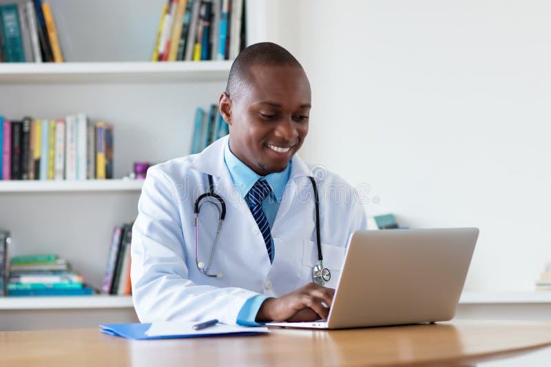 Arzt für Allgemeinmedizin des Afroamerikaners, der am Computer arbeitet lizenzfreies stockfoto