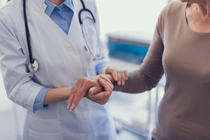 Arzt für Allgemeinmedizin hält weibliche Hand im Krankenhaus stockbilder