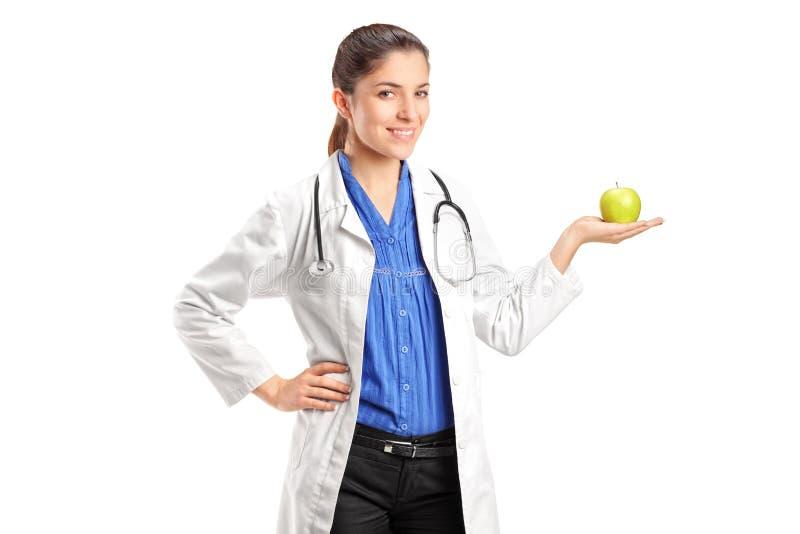 Arzt mit dem Stethoskop, das einen Apfel anhält lizenzfreie stockfotografie