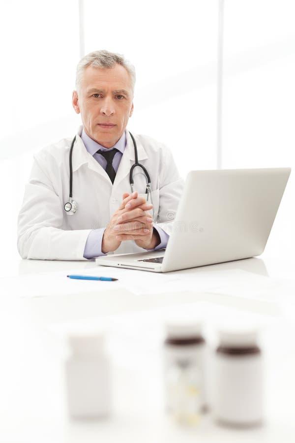 Arzt. Reifer Doktor, der an seinem Arbeitsplatz mit sitzt stockfotos