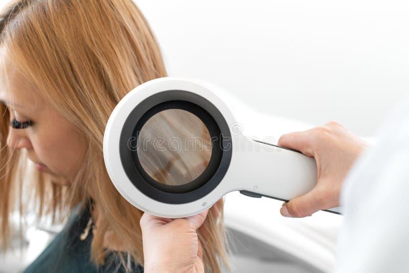 Arzt Trichologistdermatologe überprüft den Zustand des des Haares Patienten und der Haarwurzeln mit einem dermatoscope stockbild