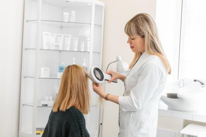 Arzt Trichologistdermatologe überprüft den Zustand des des Haares Patienten und der Haarwurzeln mit einem dermatoscope lizenzfreie stockfotografie