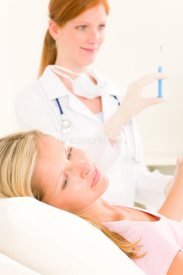 Arzt wenden Einspritzung am Frauenpatienten an stockbild