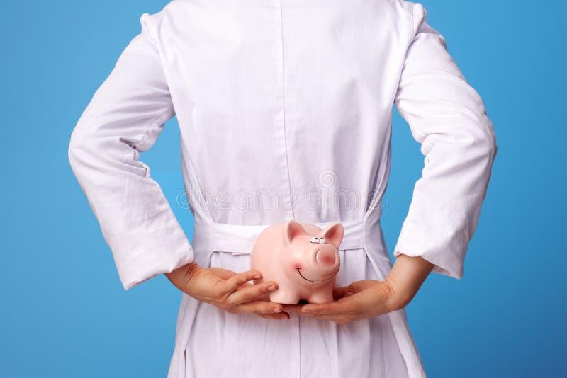 Arztfrau, die piggybank hinten hält, unterstützen auf Blau stockfotografie
