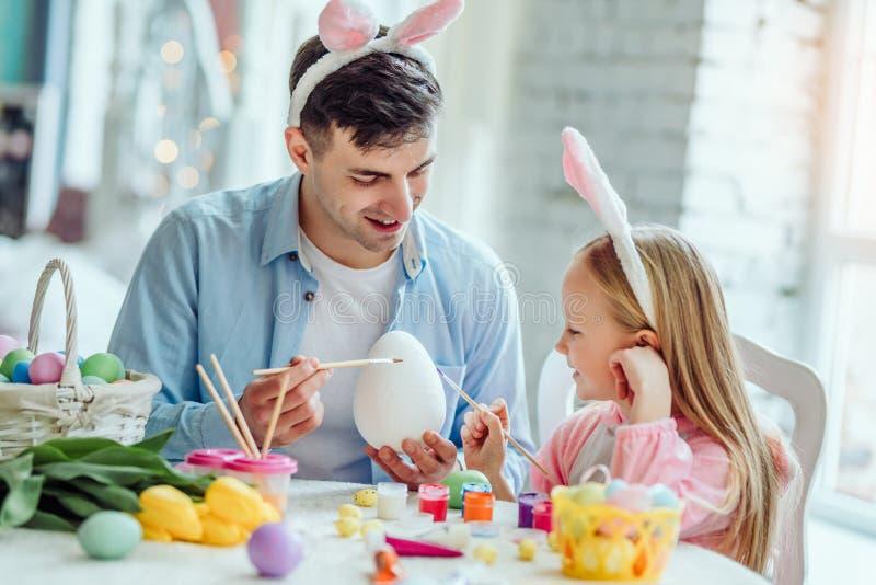 Así como papá pintaremos un huevo de Pascua grande El papá y su pequeña hija junto se divierten mientras que se prepara por los d fotografía de archivo libre de regalías