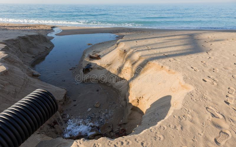 As águas residuais industriais, o encanamento descarregam o desperdício industrial líquido no mar em uma praia da cidade Fluxos s foto de stock royalty free