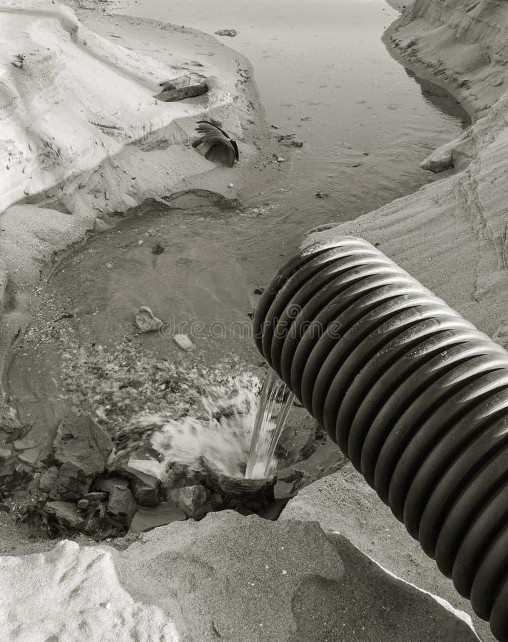 As águas residuais industriais, o encanamento descarregam o desperdício industrial líquido no mar em uma praia da cidade Fluxos s fotos de stock